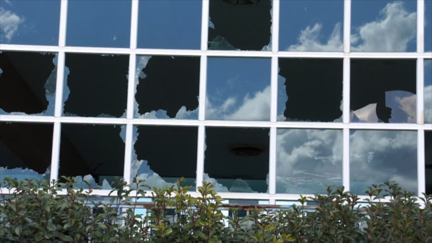 A blue sky with fluffy white clouds moving rapidly across it, reflected in the numerous panes of a large glass wall, many of which are broken. - HD stock footage clip