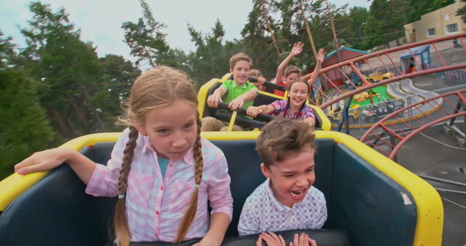 Group of kids shouting while riding a roller coaster