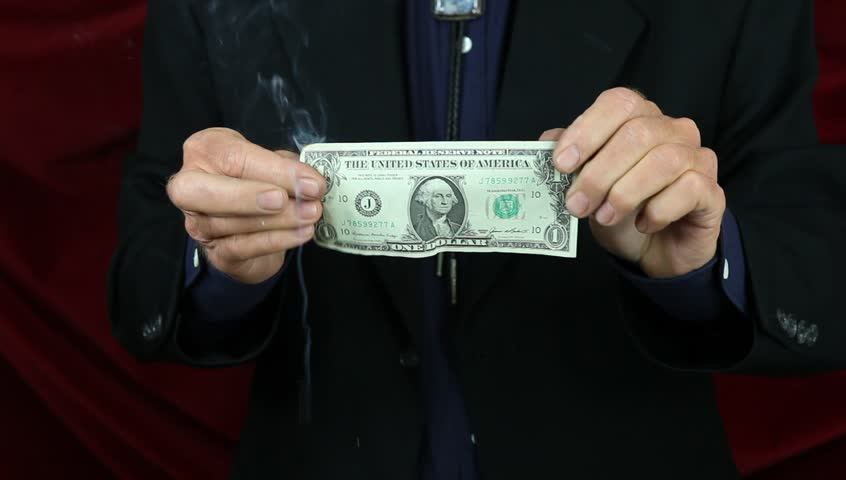 Magician creates money from fire. - HD stock footage clip