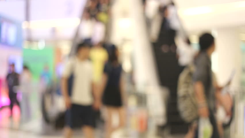 People on moving escalators at modern shopping mall Blur effect