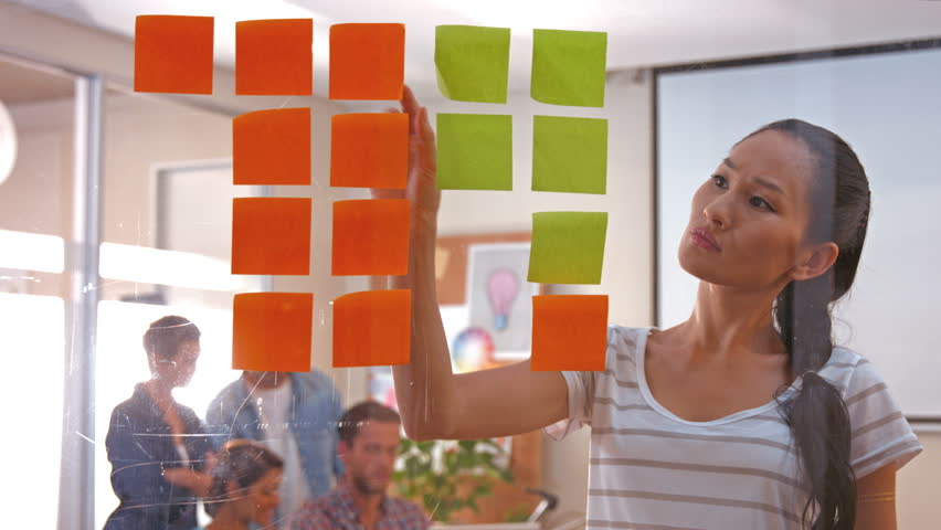 Casual businesswoman looking at post it with her colleagues behind in office - 4K stock video clip