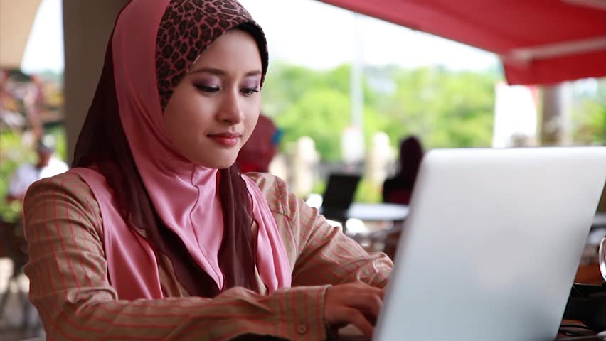 Young Muslim Girl using laptop and smiling at the camera - HD stock video clip