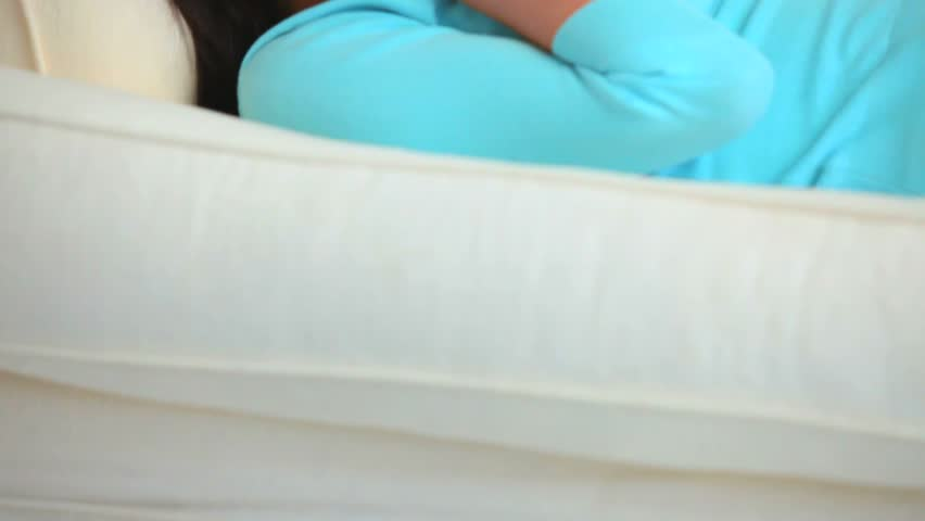 Young woman listening to music with headphones lying down on the couch - HD stock footage clip