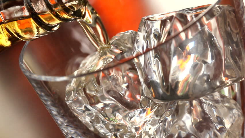 Pouring a scotch whiskey on the rocks close up - HD stock footage clip