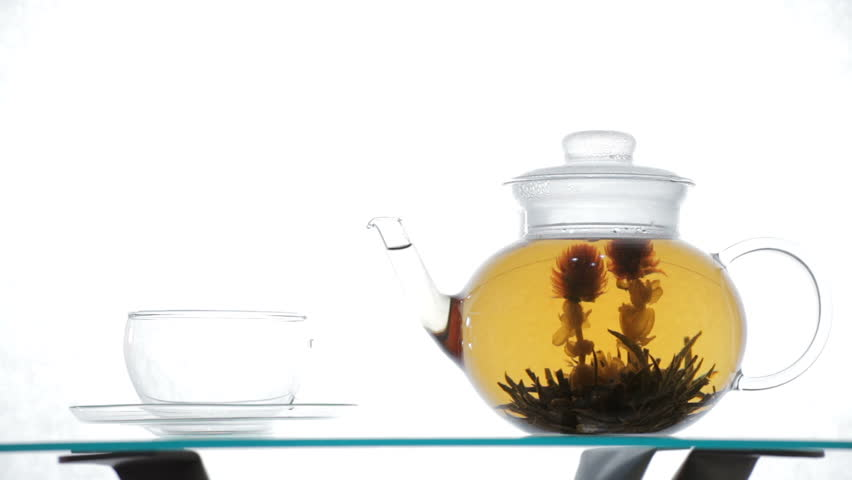 Woman pours Green Chinese flower tea from glass teapot into glass