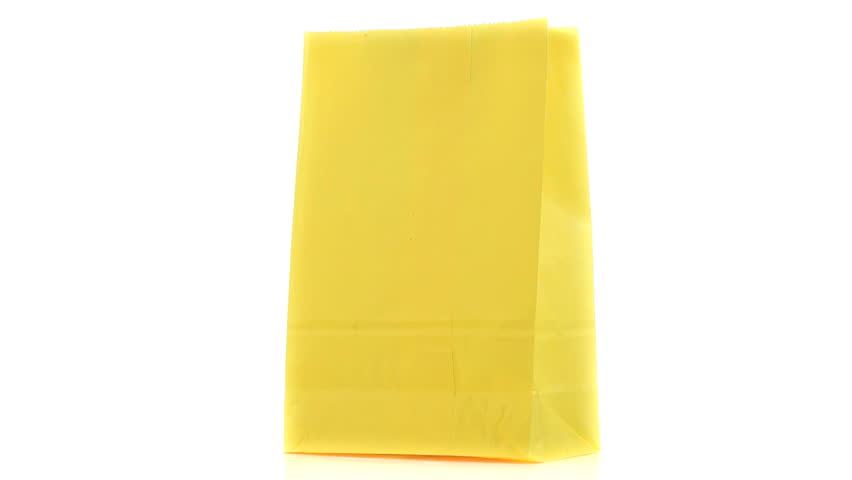 Yellow shopping bag turning on itself on a white background - HD stock footage clip