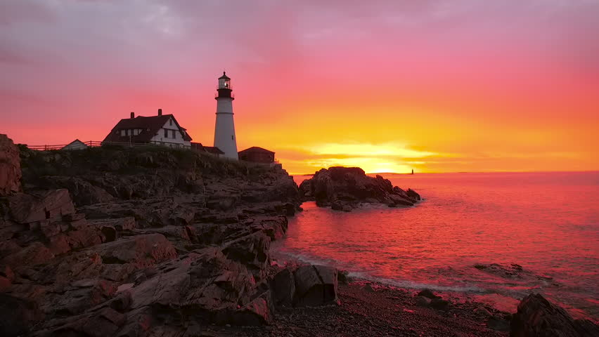 Establishing aerial shot of a gorgeous sunrise in Maine capturing a Lighthouse. Vivid colors of purples, pinks and yellows are reflected in the water. - HD stock video clip