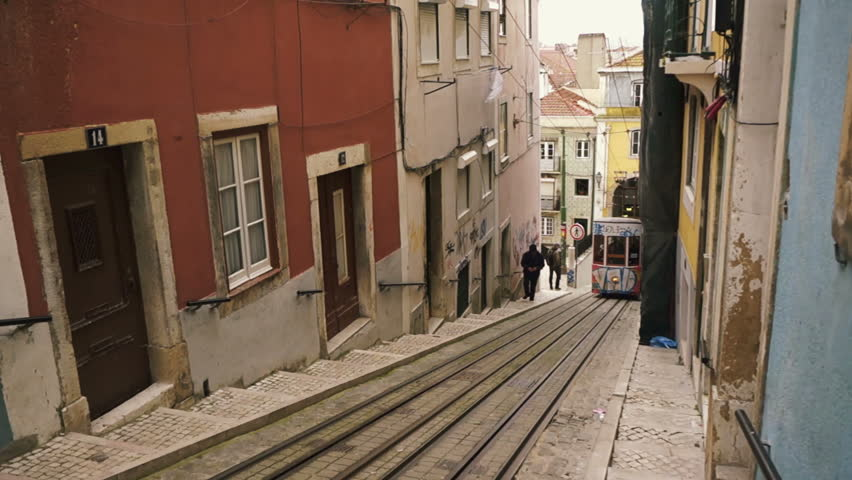 Lisbon, Portugal - March 25th, 2013: Tram car driving uphill out of a tunnel on narrow gauge rails through a narrow alley in Lisbon, Portugal