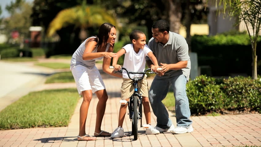 Cute young african-american boy being encouraged by his parents as he practices riding his bicycle - HD stock video clip