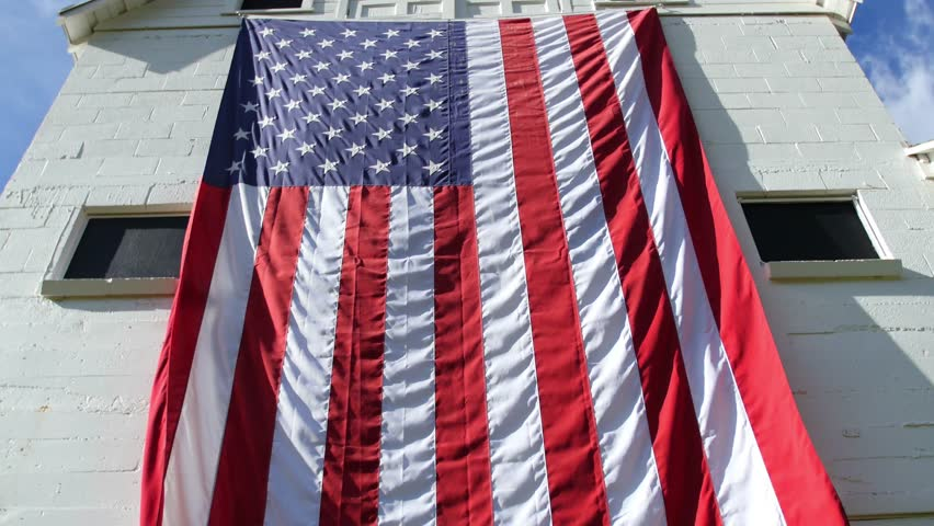 A large American flag blows in the wind on an old white barn. - 4K stock footage clip