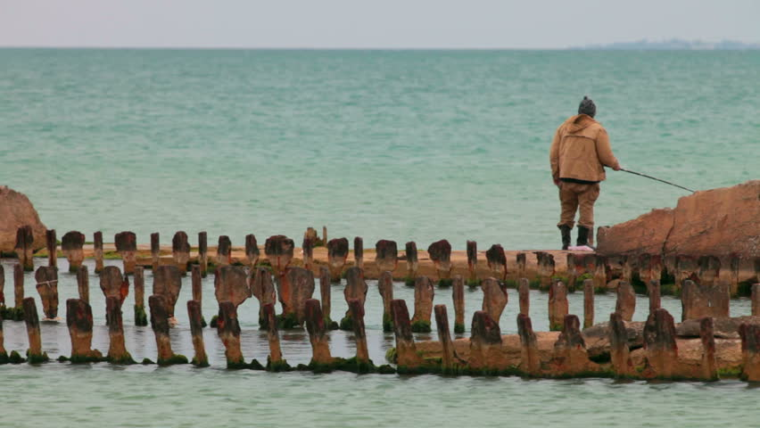 fisherman on the old destroyed  rusty pier