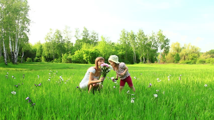 Young mother and child with flowers in the field. Look at Camera. Dolly  - HD stock footage clip