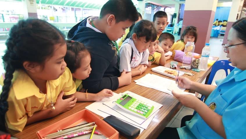 Elementary Classrooms Writing ~ Teacher writing on blackboard at elementary school stock