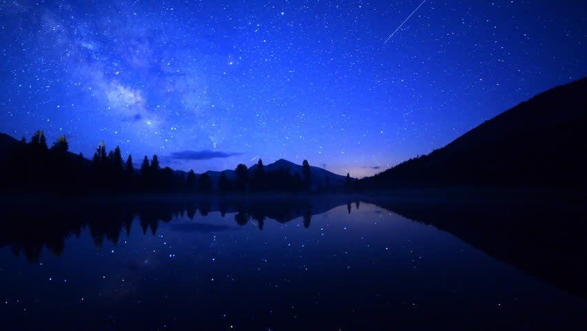 Astrophotography Time-lapse footage with pan left motion of milky way galaxy spanning over reflective alpine lake in Yosemite National Park, California