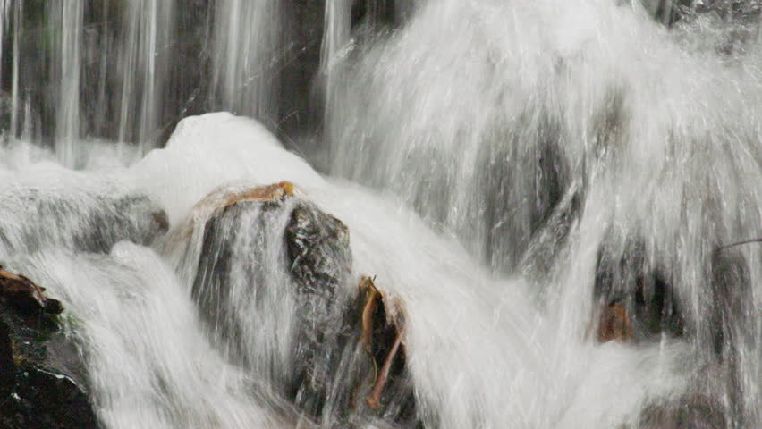 Rio de Janeiro, Brazil - June 2013: Extreme close up of water splashing at the base of a small waterfall in a botanical garden. Shot in Rio, Brazil.