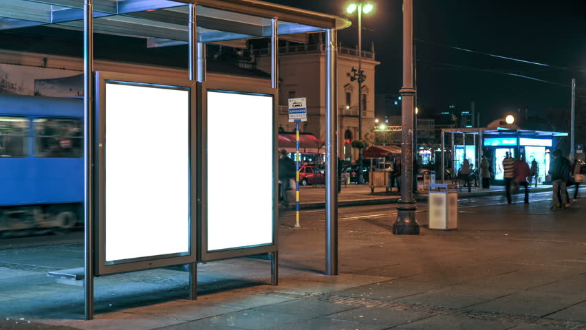 Ad space at the tram station at night. People pass by and watch. It is easily applied poster on a blank white background. Zagreb, Croatia - The main railway station