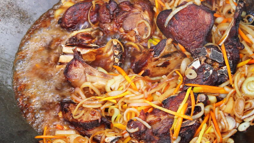 Meat frying with onion and carrots in campfire Cauldron. Closeup. - HD stock video clip
