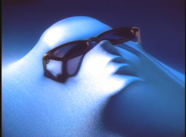 Face covered with blue fabric wearing sunglasses while light moves around - SD stock video clip