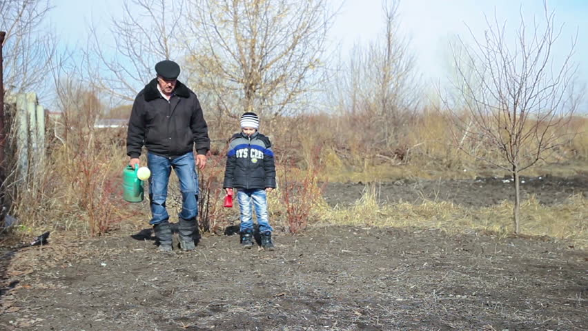 Grandfather  with his grandson in the early spring are watering the trees and bushes in the garden