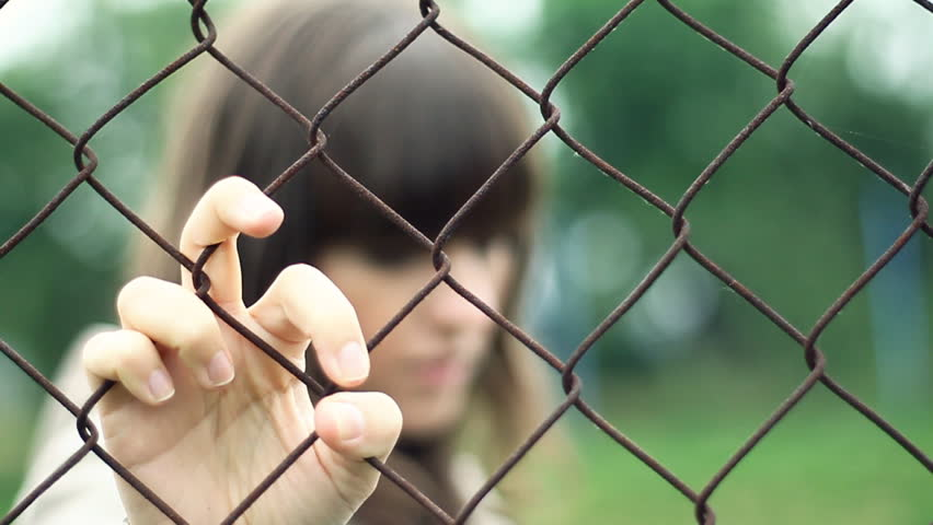 Sad woman behind chain-link fence, outdoors  - HD stock video clip