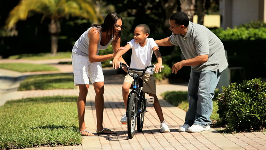 Loving african-american parents teaching their young son to ride a bicycle - HD stock footage clip
