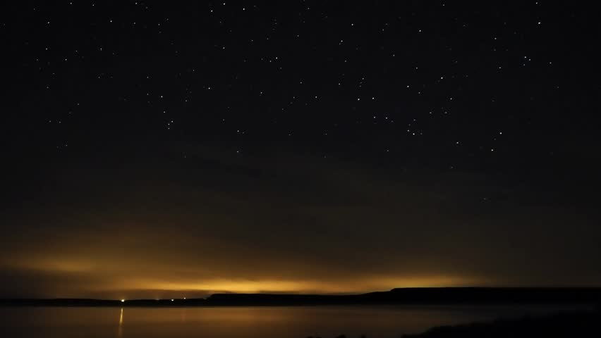 Stars tracking across the night sky until dawn (time lapse) with wispy clouds on the horizon.  Overlooking the sea/lake.