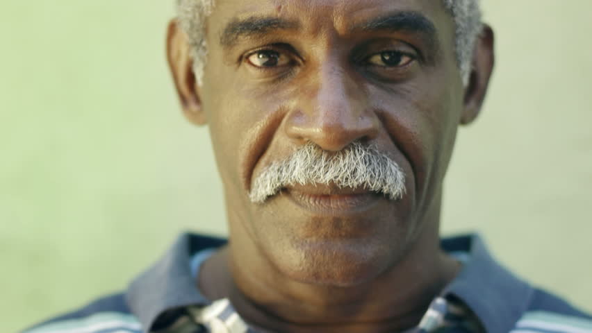 Portrait of old black man with mustache looking at camera against green wall and smiling. Senior african american people #1267435