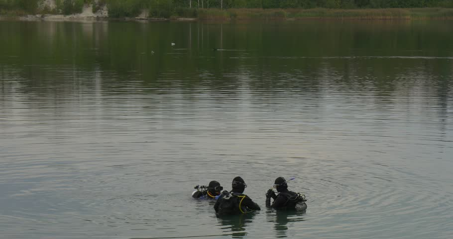 Three Divers Distantly are Standing in the Water, Checking their Equipment, Talking, Going to Dive, Men, Divers in Swimwear, black suits, aqualungs, are diving into the pond, lake, river, overgrown - 4K stock footage clip