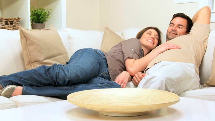 Happy caucasian couple relaxing stretched out on their sofa at home - HD stock footage clip