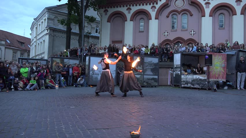 VILNIUS, LITHUANIA - JUNE 19, 2015: Amazing fire show with young artists couple juggle burning flame torches on June 19, 2015 in Vilnius, Lithuania. Static shot. 4K