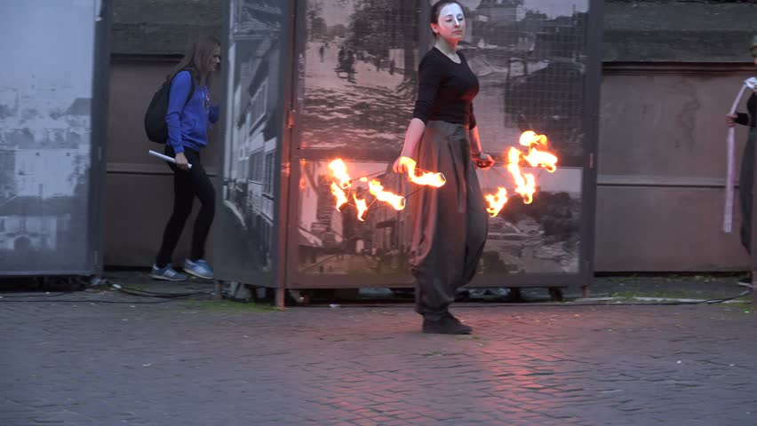 VILNIUS, LITHUANIA - JUNE 19, 2015: Artistic woman with burning torch start spectacular fire juggle performance for people audience on June 19, 2015 in Vilnius, Lithuania. Follow shot. 4K