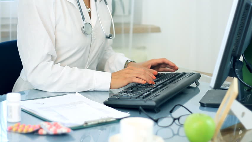 Female doctor working on computer and checking medications - HD stock footage clip