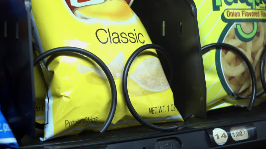 USA - CIRCA 2015: Small Bag of Classic Lays Potato chips purchased from vending machine, showing a typical daily snack of someone in the United States of America, shot in 4k resolution, taken in 2015.