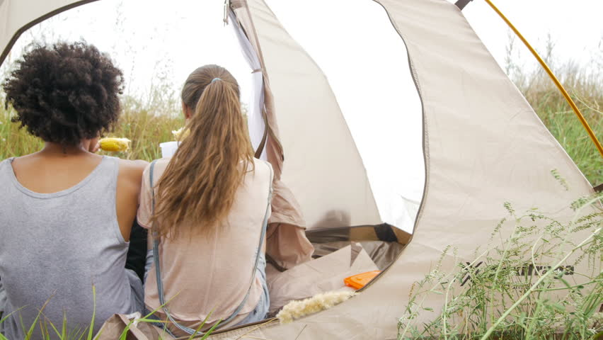 Mixed race couple sitting in their tent, talking, eating corn and looking at the sea. Hippie's tent located on a green hillside. They have a great time together.
