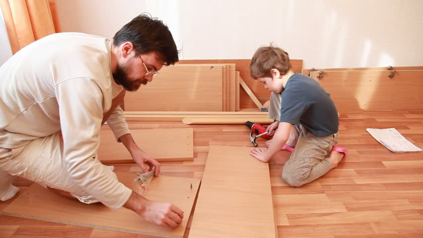 Father tightening screws in wooden board and little boy works with hammer sitting on the floor - HD stock footage clip