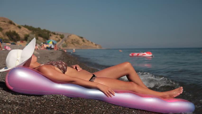 woman in white sun hat sunbathing on beach