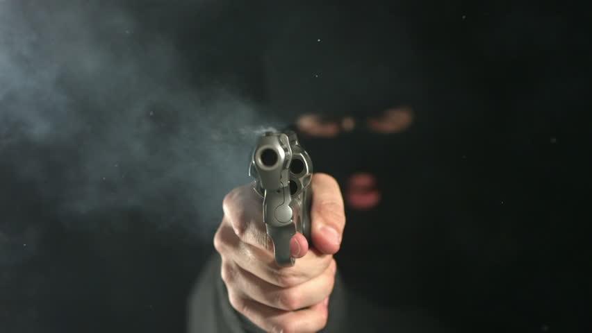 Cinemagraph - Criminal shoots gun directly at camera, slow motion. Looping Motion Photo.
