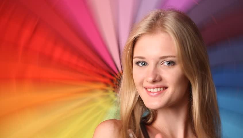 Beautiful blond female rotating rainbow umbrella behind her back - HD stock footage clip