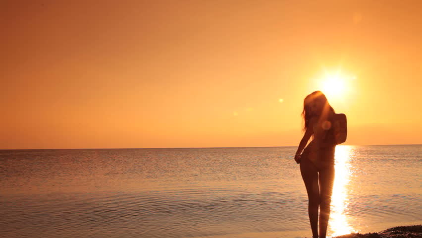 Woman on a quiet beach at sunset - HD stock footage clip