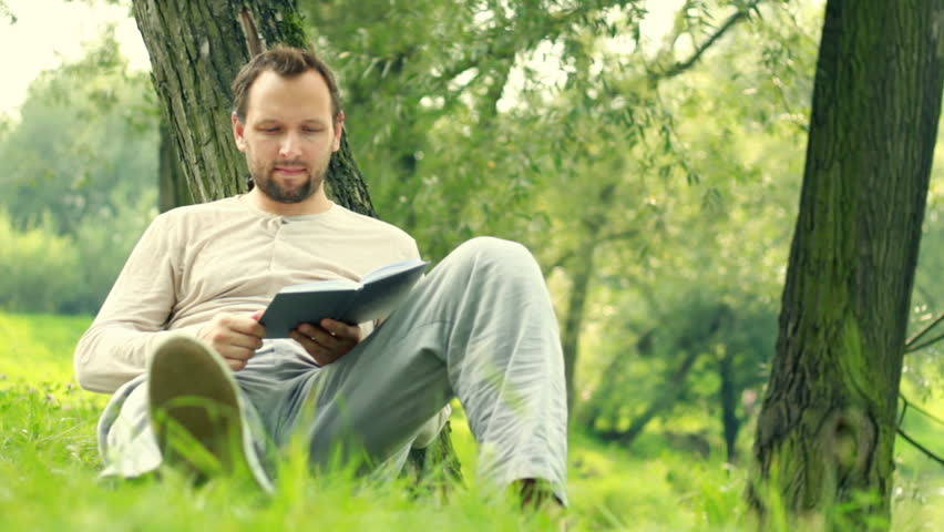 Young man reading book in the park, dolly shot - HD stock footage clip
