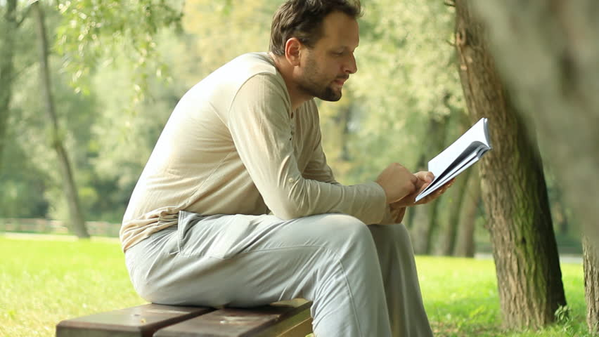 Young man reading book in the park - HD stock footage clip