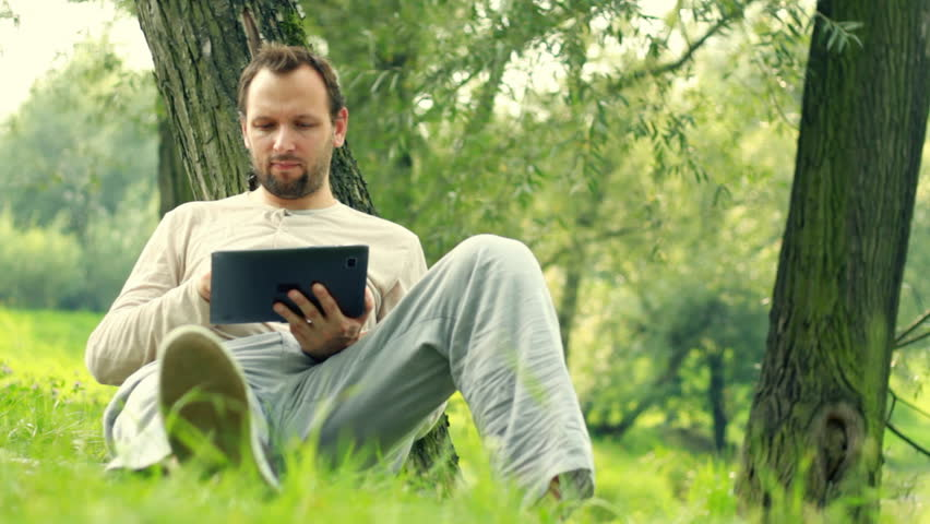 Young happy man with tablet computer by the tree in park, dolly shot - HD stock video clip