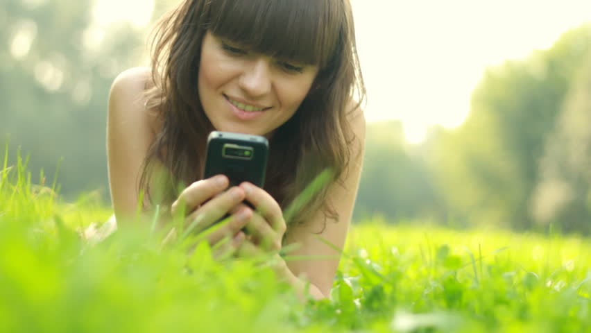 Young woman lying on the grass and sending sms, texting in the park - HD stock video clip
