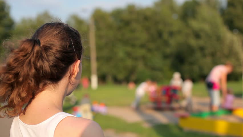 Young woman looking at a playground with children - HD stock video clip