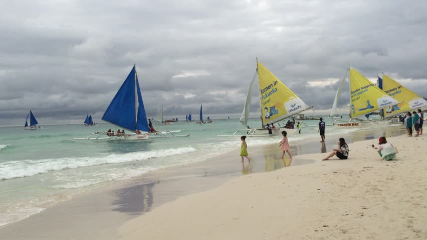 BORACAY, PHILIPPINES - OCT 3, 2014: Tourists enjoying with many sail boats on the beach in Boracay island, Philippines.
