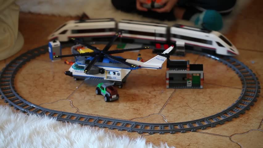 ROME, ITALY - DECEMBER 28, 2015: Child playing with the high-speed passenger train from LEGO CITY and LEGO helicopter. Lego is a popular line of construction toys manufactured by the Lego Group.