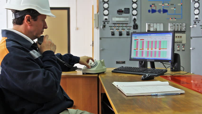 engineer sits at table workplace and talks to someone by phone, close-up - HD stock video clip