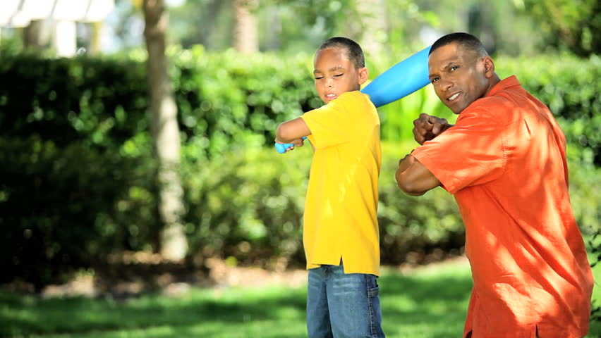 Young african american father teaching his son how to swing a baseball bat