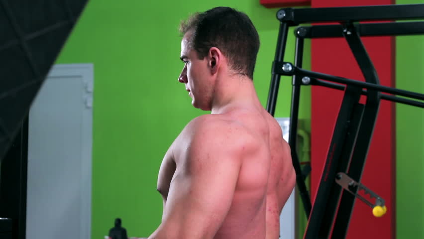 Workout for young bodybuilder. Exercises for arms and back with exercise equipment