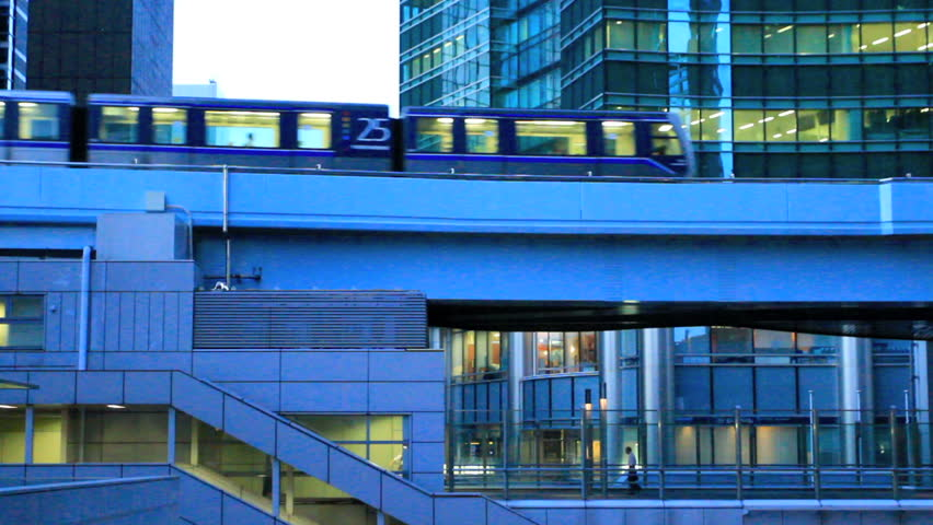 Riding the train with modern office buildings in the background.